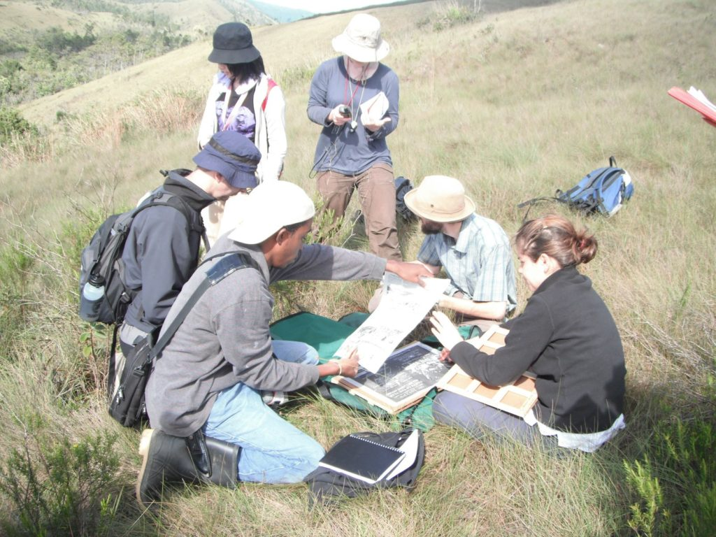 A group of six students, 3 men & 3 women, gather around a plant press on a grass-covered hillside, distant grass and tree covered hills can be seen in the background.