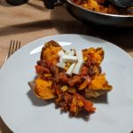 A picture of one of the completed dishes. A sweet potato topped with vegetable chilli and cheese