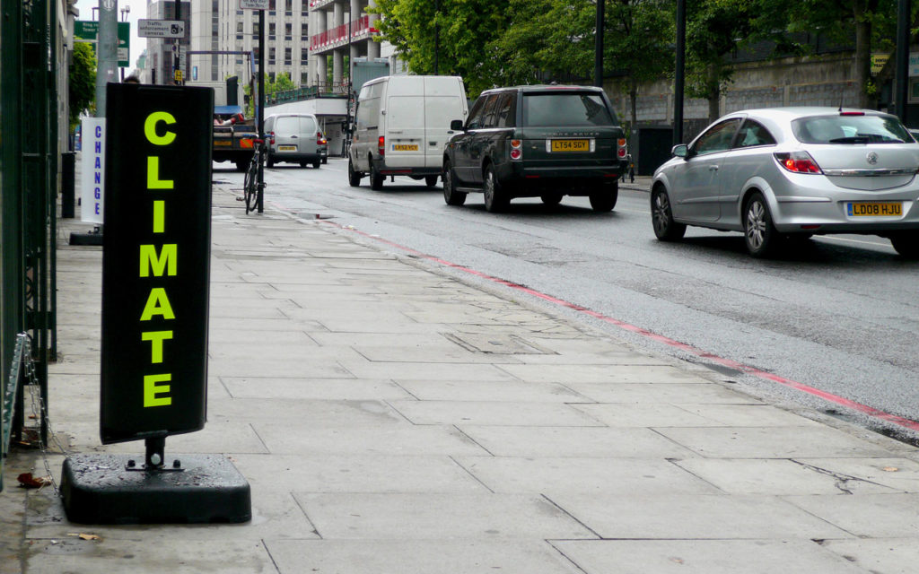 A busy street in London, on the right hand side there is a traffic queue of cars on a black tarmac road, with buildings visible in the distance. On the left there is a wide section of pavement. At the far left, in the foreground is a black spinning sign - reminiscent of a bureau de change sign. We can see one side of the sign, which reads 'CLIMATE' in neon yellow capital letters. Some distance behind this sign is another sign. This second sign it white, and vertically reads 'CHANGE' in bright blue capital letters.