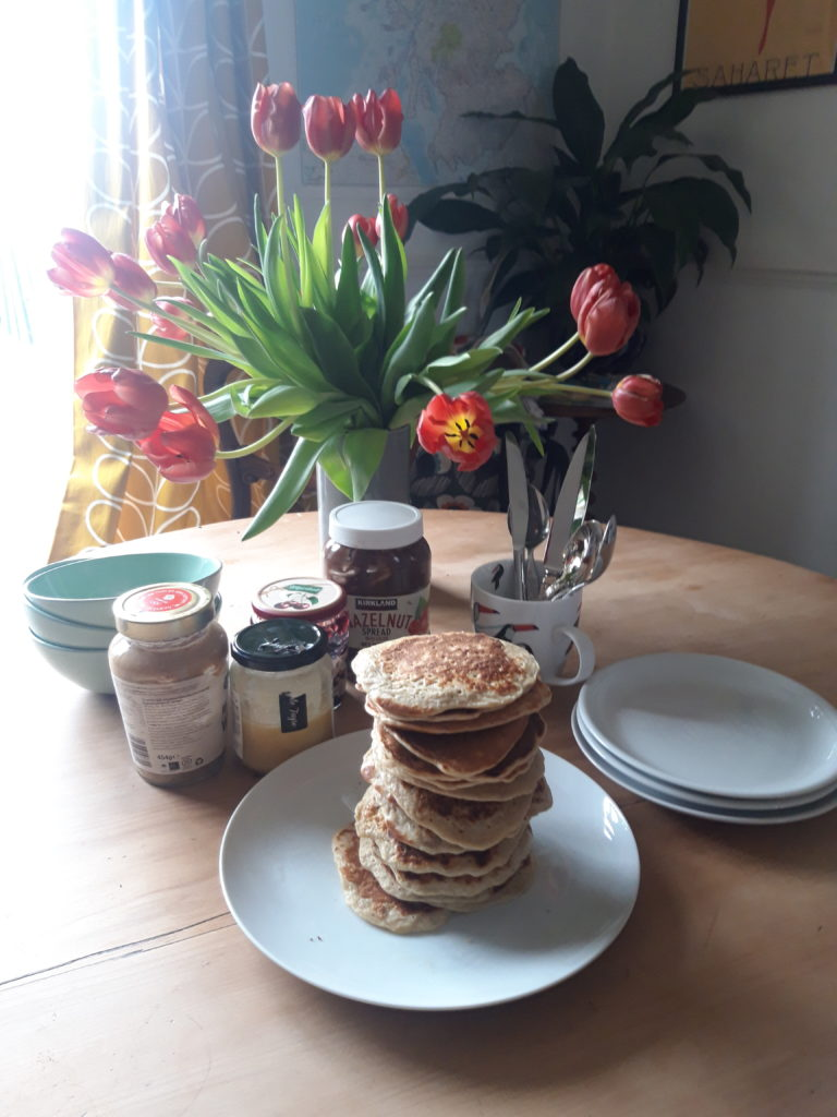 A wooden dining table near a bright window set with red tulips in a vase, some jams, 3 stacked blue ceramic bowls, stacked white side plates, some cutlery and a white serving dish with a tower of bananna pancakes.