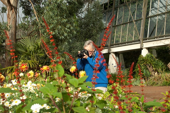 Photograph of Brenda White taking a photograph outside the RBGE Glasshouses