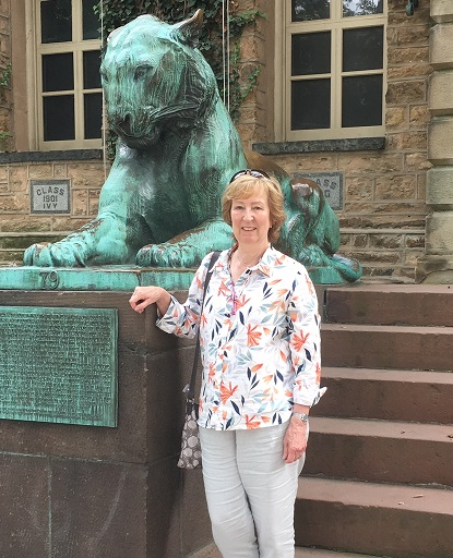 Photographic portrait of Laura Gunstensen standing beside stone steps and a copper lion