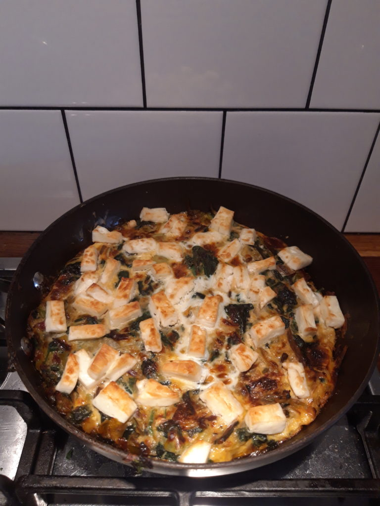 A pan of fritatta topped with feta cheese sitting on a kitchen surface.