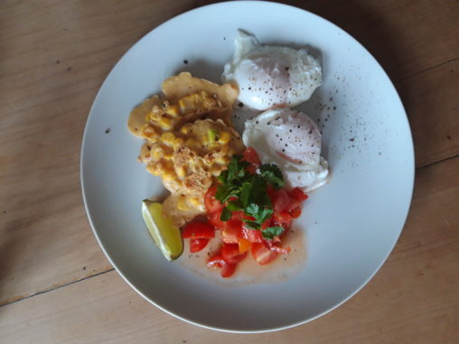 A plate of sweetcorn fritters served with poached eggs and tomato salsa on the side, gardnished with coriander and a slice of lime.
