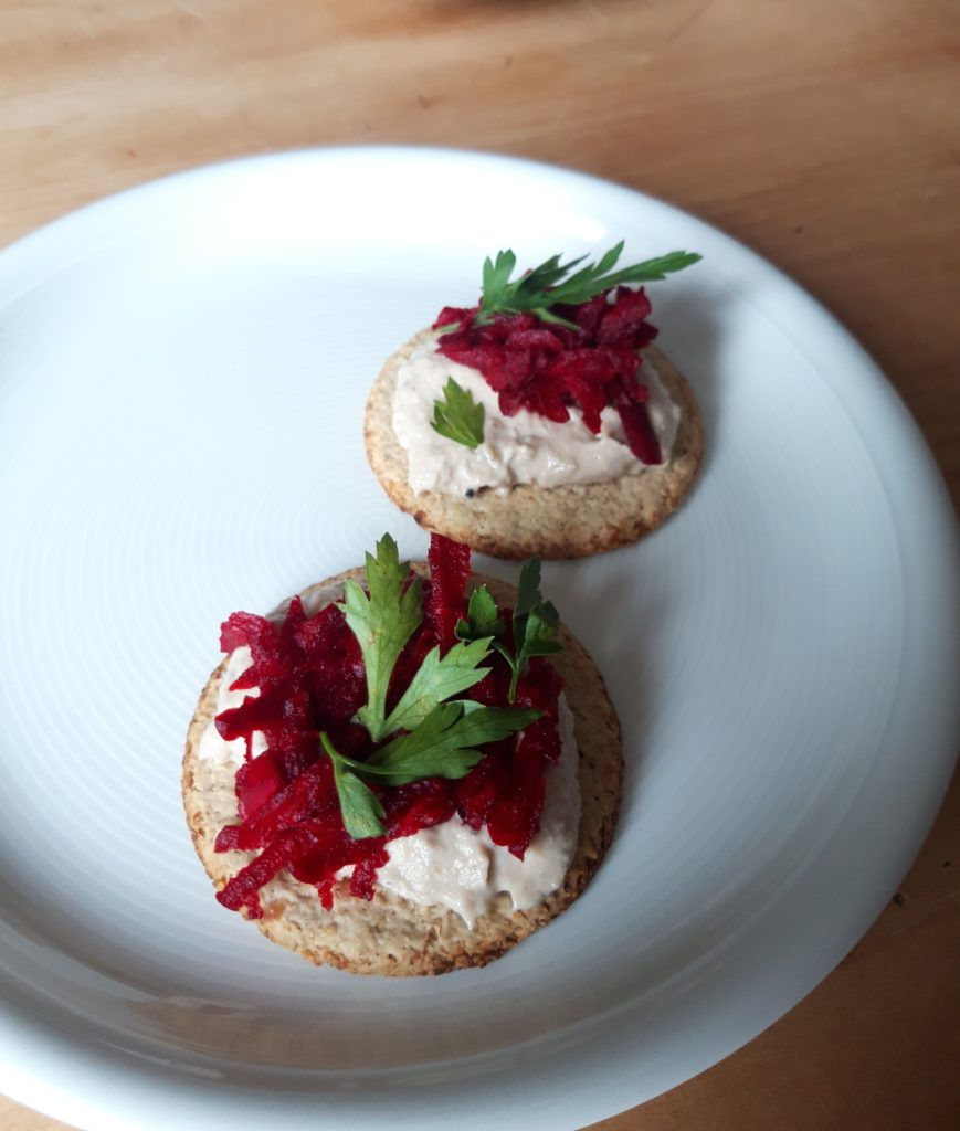 A plate of oatcakes topped with smoked mackerel pate and beetroot.