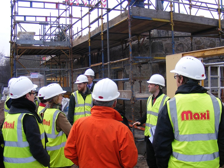 image shows a building construction site with scaffolding, there are a group of visitors standing listening to a lecture and they are wearing yellow high vis jackets with Maxi written on them and all wearing white safety hardhats.