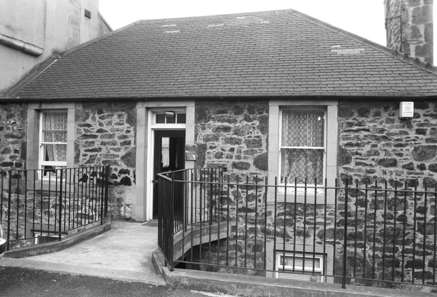 image shows a black & white image from the 1990's of the upper floor of the stone Cottage at road level with a front door and a window either side. You can just see a glimpse of the lower floor windows. There are black wrought iron railings at the front either side of the entrance way and the Cottage has a grey slate roof.