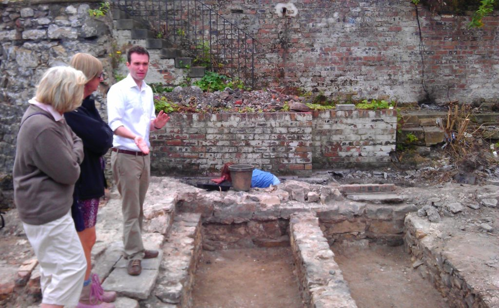 image shows a gentleman in a white shirt at the edge of a stone lined archaeology pit he is explaining the project to two visitors to his side who are listening attentively.
