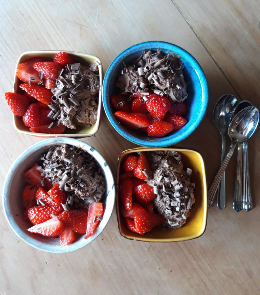 Four brightly coloured bowls of chocolate mousse topped with chocolate shavings and strawberries
