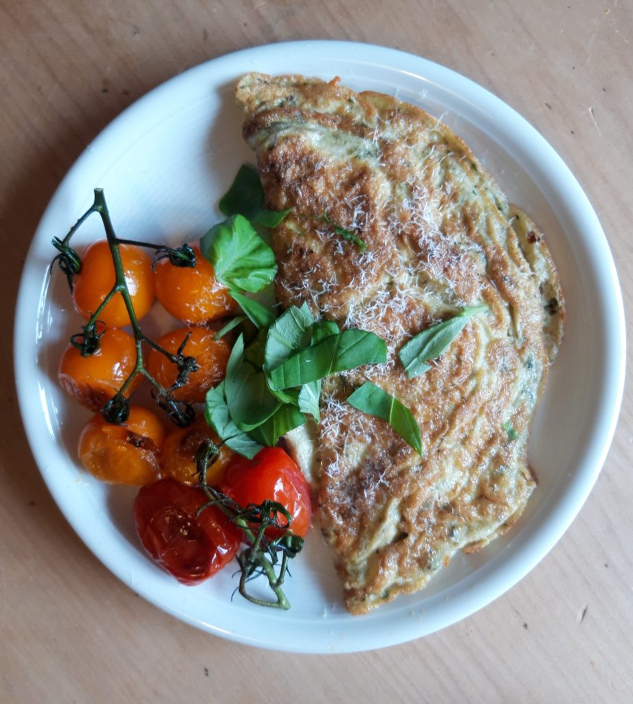 A plate with an omelette and roasted vine tomatoes