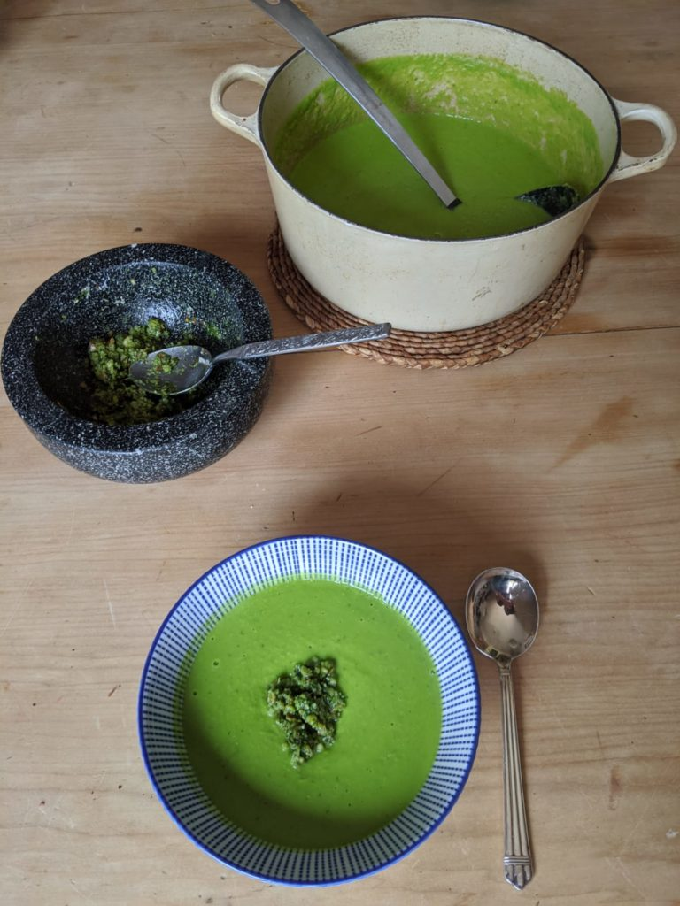 Photo shows a bowl of bright green pea soup topped with pesto. Also shown is the pestle and mortar which has been used for making the pesto.