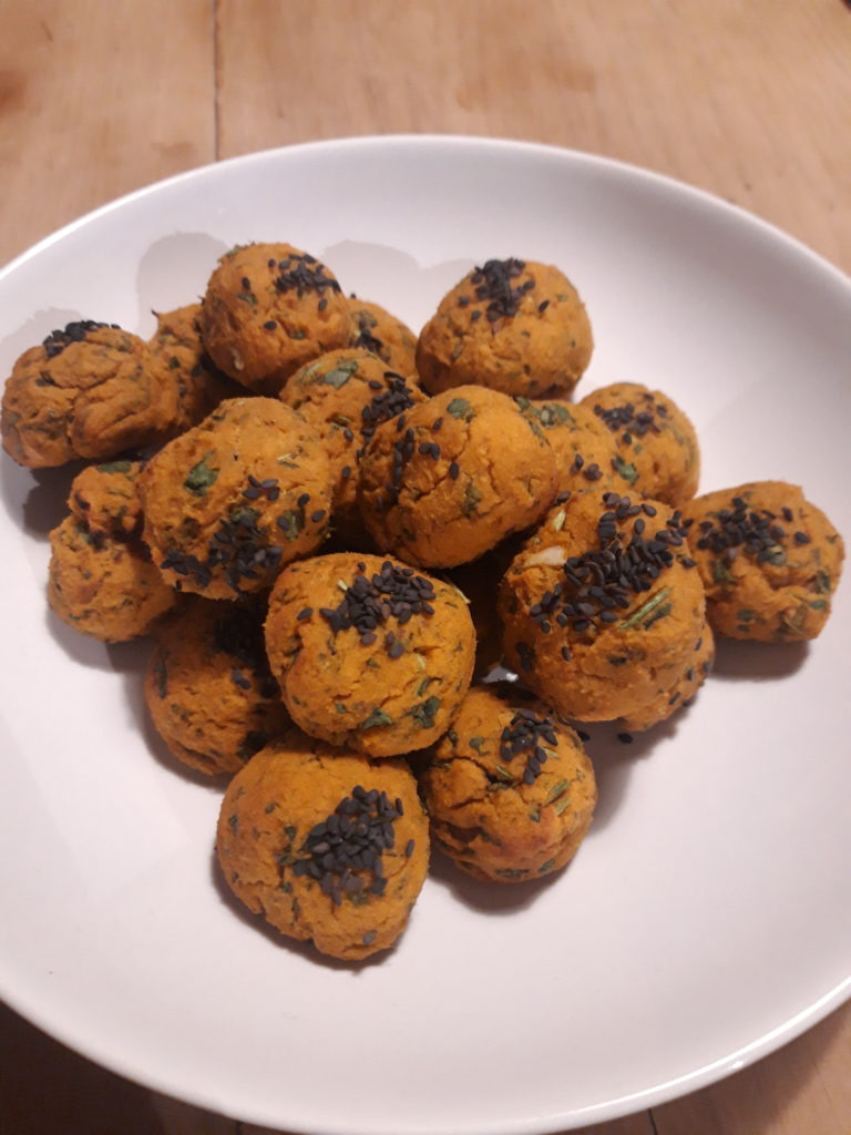 Image shows a plate of falafel balls made from sweet potato and topped with sesame seeds