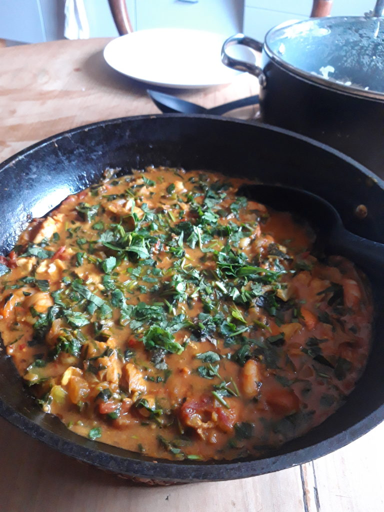 Image shows a large bowl of curry topped with lots of fresh herbs