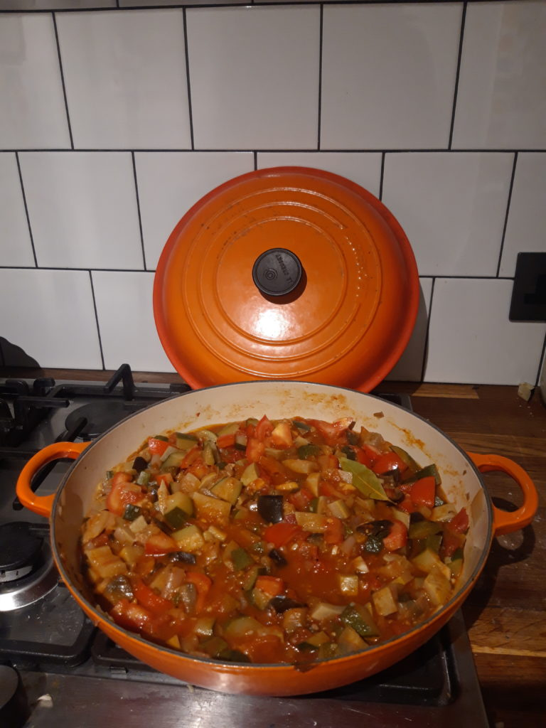Image shows a pan of ratatouille, made vegetables and tomatoes, cooking on the hob