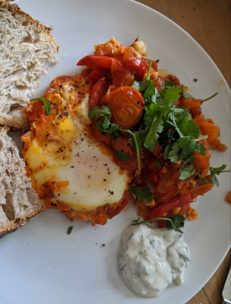 Image shows a dish of bread, a fried egg and shakshuka a vegetarian dish made with tomaotes
