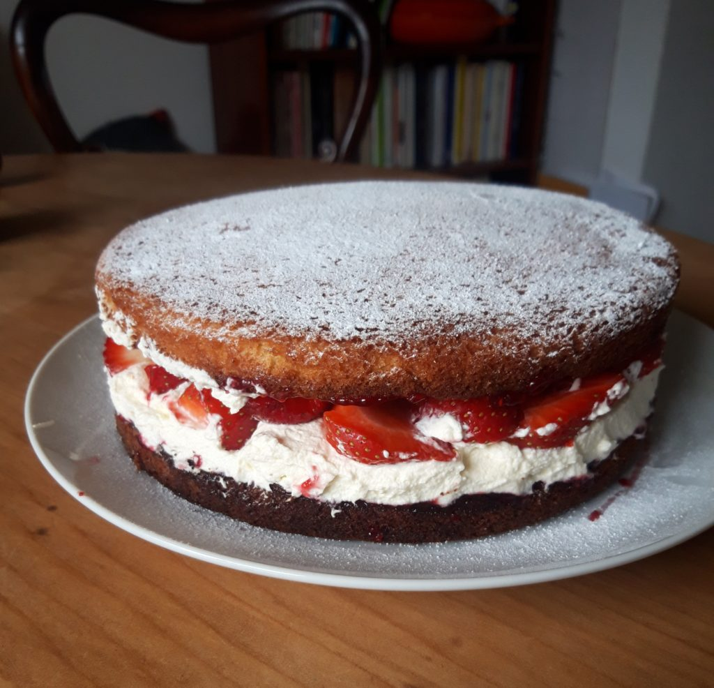Image shows a sponge cake that has been filled liberally with strawberries and cream
