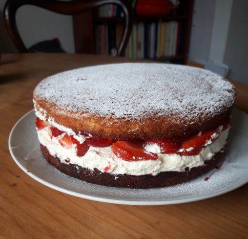 Image shows a large sponge cake filled with cream and strawberries