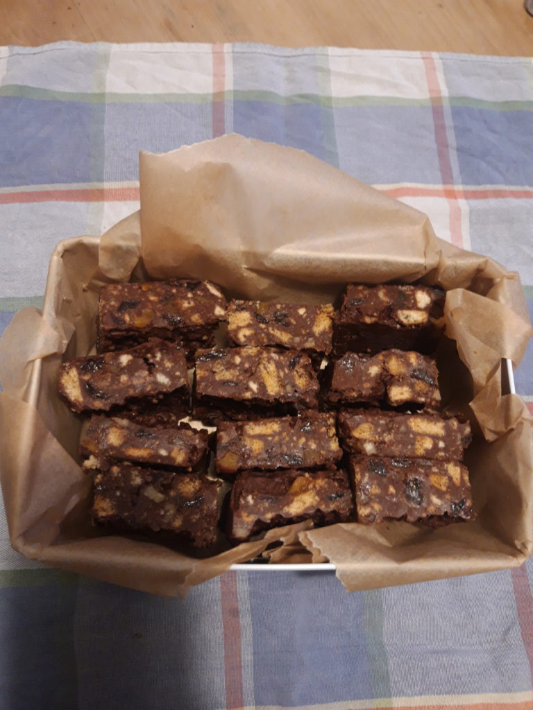 Image shows a tin of tiffin squares on the dining table