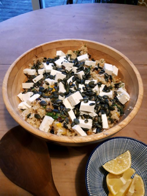 a bowl of bulgar wheat salad made with squash, feta cheese and seeds