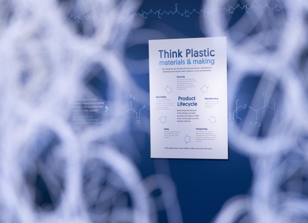 View of Think Plastic exhibition in the John Hope Gateway. The foreground is blurry, with a work made out of looped and intertwined white plastic just visible. Through this, a sign is visible - The title reads: Think Plastic materials and making, and below that 'Product Lifecycle'. Around 'Product Lifecycle', five pieces of texts are arranged cyclically, with an arrow between each section of text. This white sign is set against a dark blue wall. At the top of the wall, sections of what appear to be scientific equations are visible in light blue.