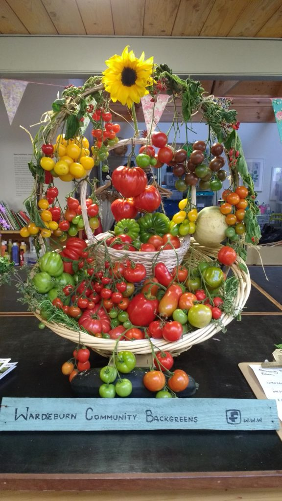 Image shows a basket of many varieties of tomatoes, decorated with greenery and a sunflower.