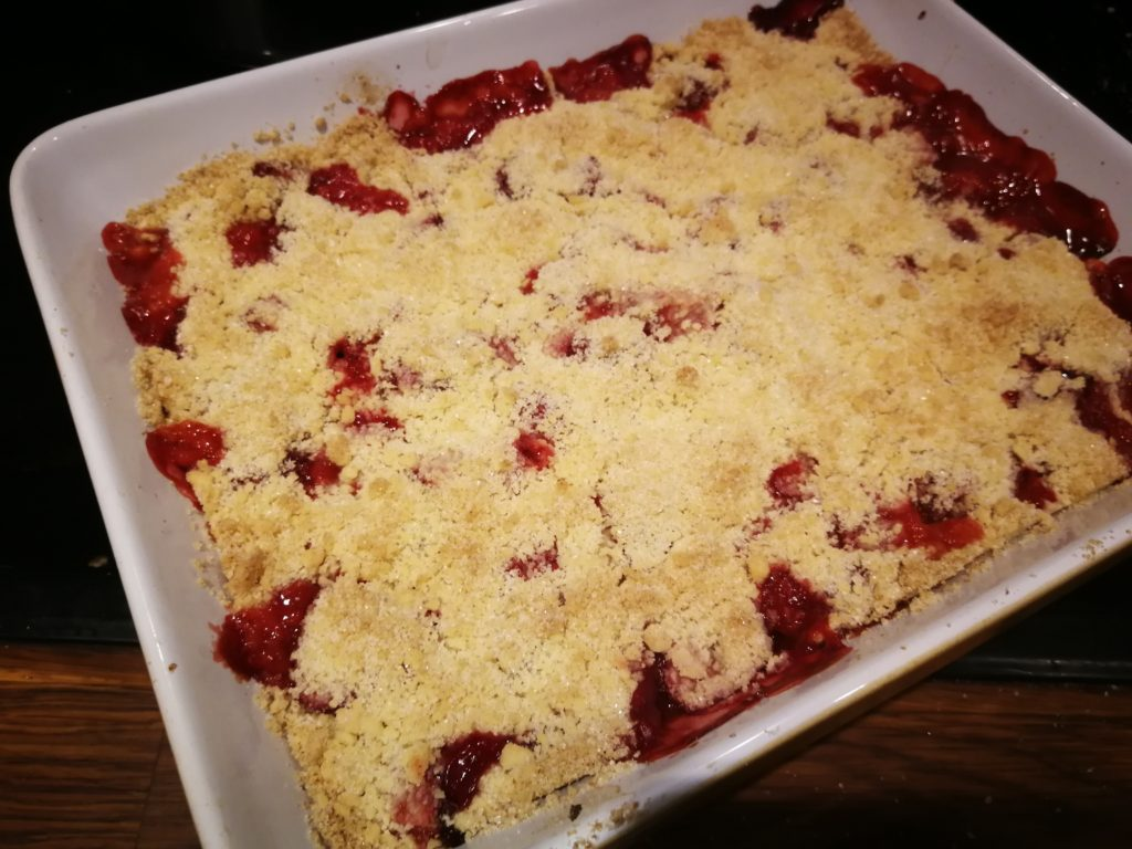Image shows a dish of strawberry crumble