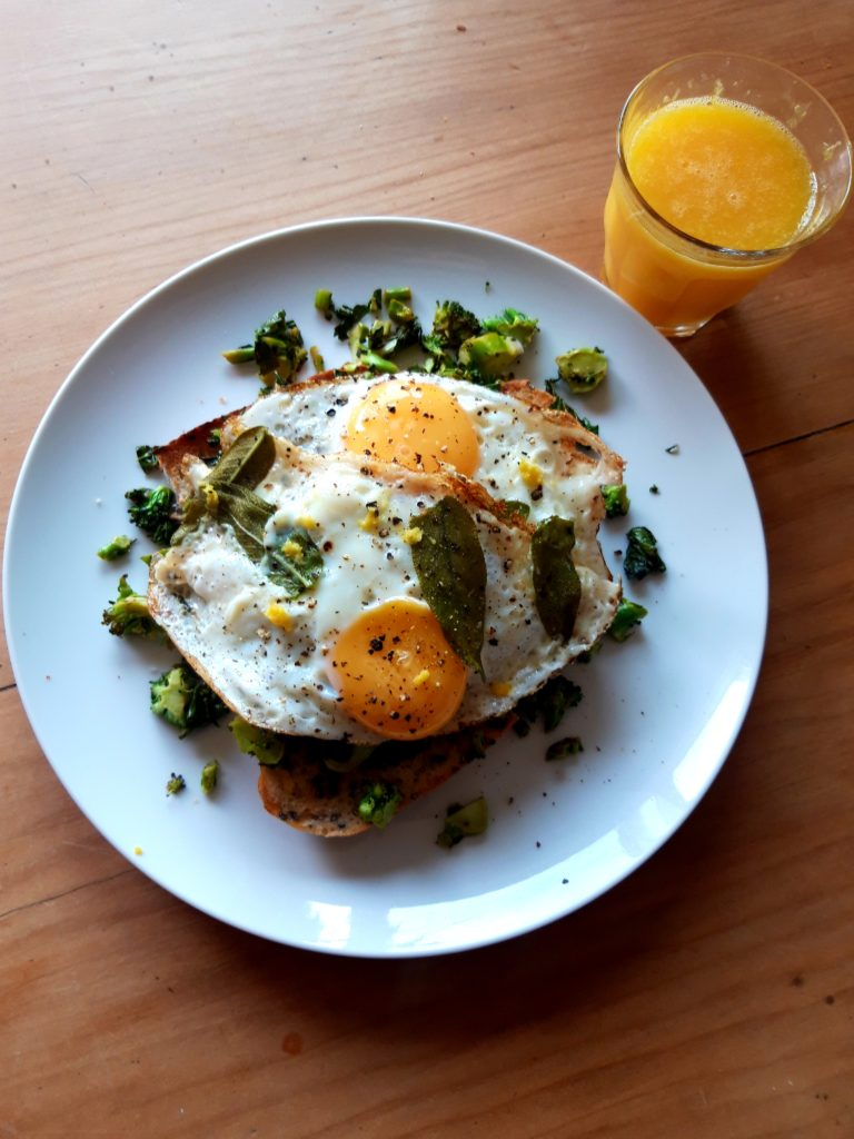 Image shows toast topped with broccoli and two eggs fried with sage