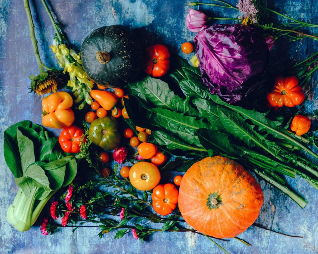 An image of a vegetable harvest of pumpkins and squashes, tomatoes, peppers, leaves, sunflower and edible flowers. Colours of vibrant orange.