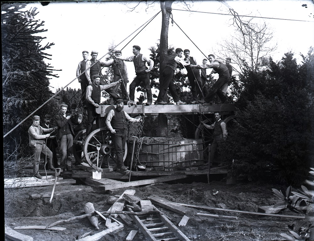 Black and white photograph showing RBGE gardeners posing on a tree in a transplanting device