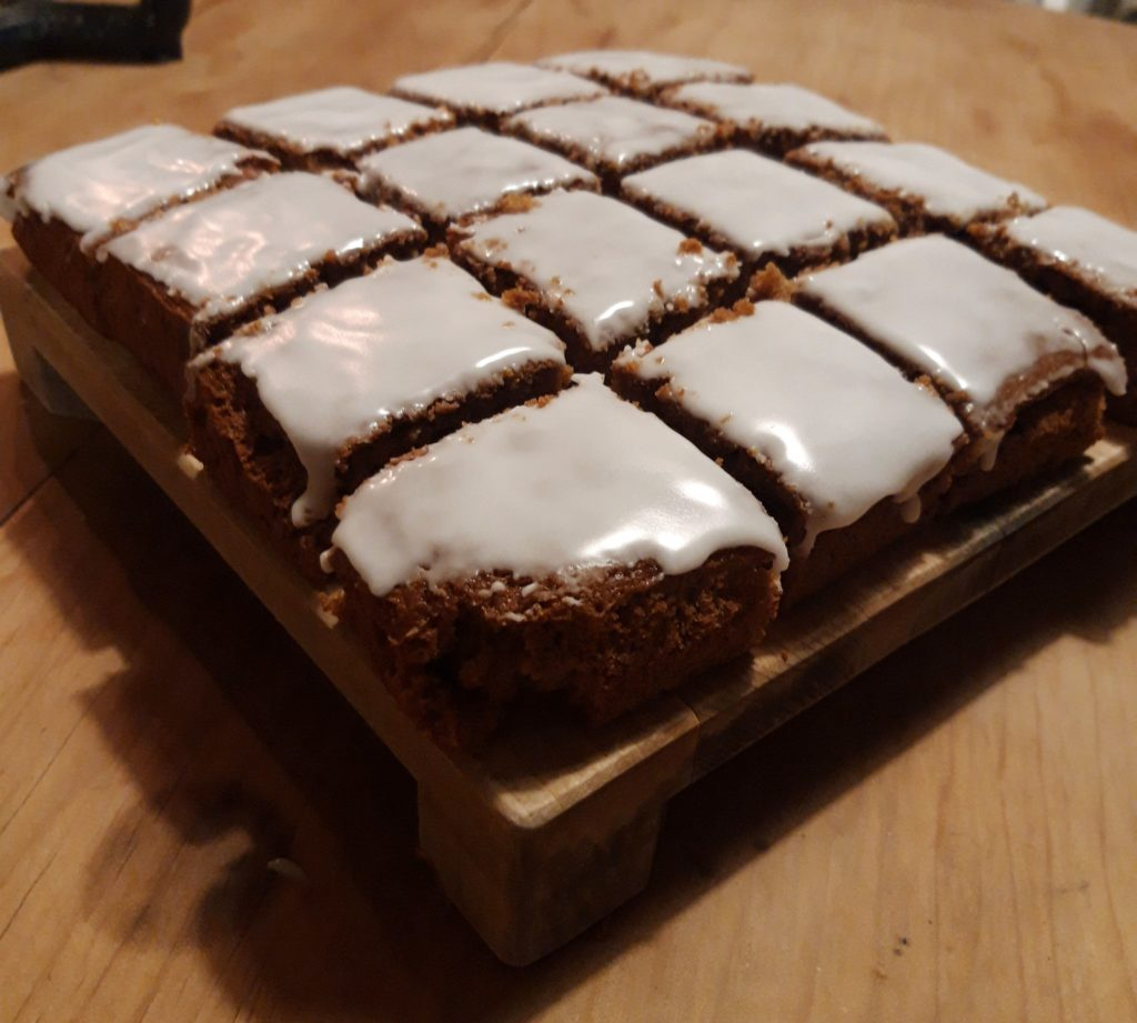 A wooden board on a pine table with cut ginger cake squares iced with white icing.