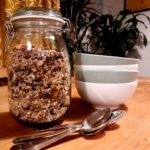 Dining table with jar of granola,spoons and bowls