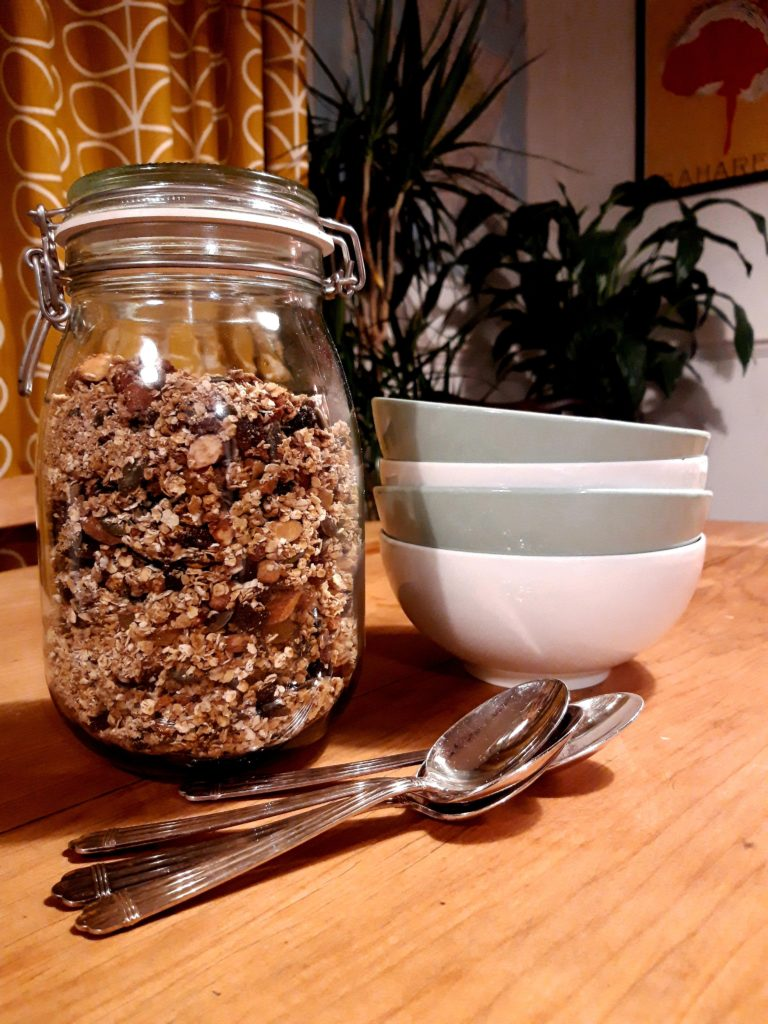 A pine breakfast table set with a clear storage jar full of granola, silver spoons and bowls.