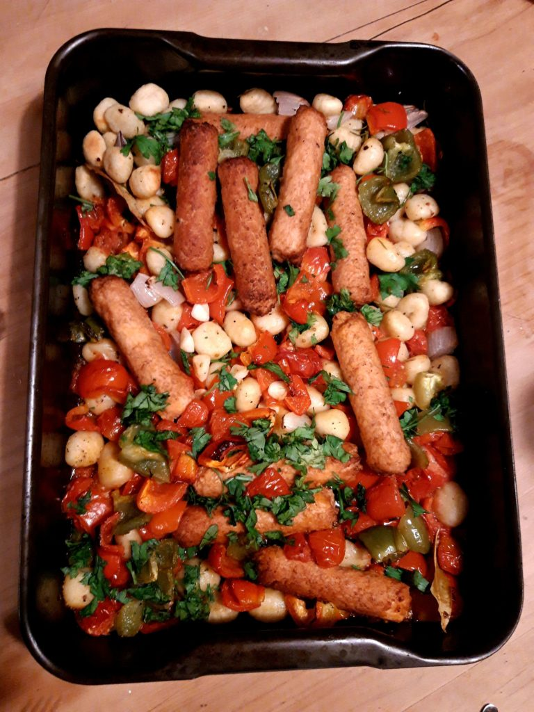 A large black baking tray on a table filled with a mix of vetetables, gnocchi and sausages