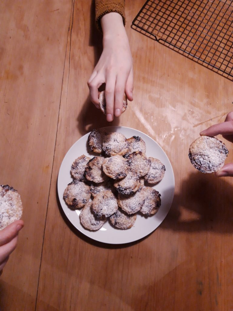 A white platter of baked mince pies on a table, sifted with white icing sugar and some people's hands reaching in for a pie.