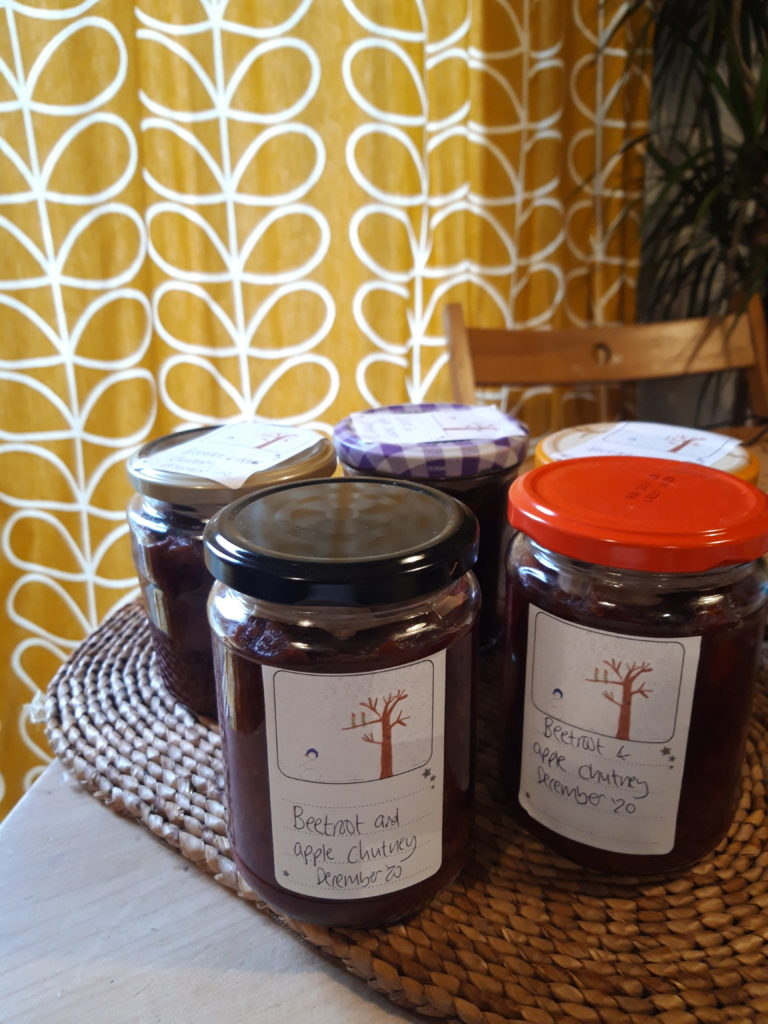 Several jars of homemade chutney with hand written labels sitting on a table.