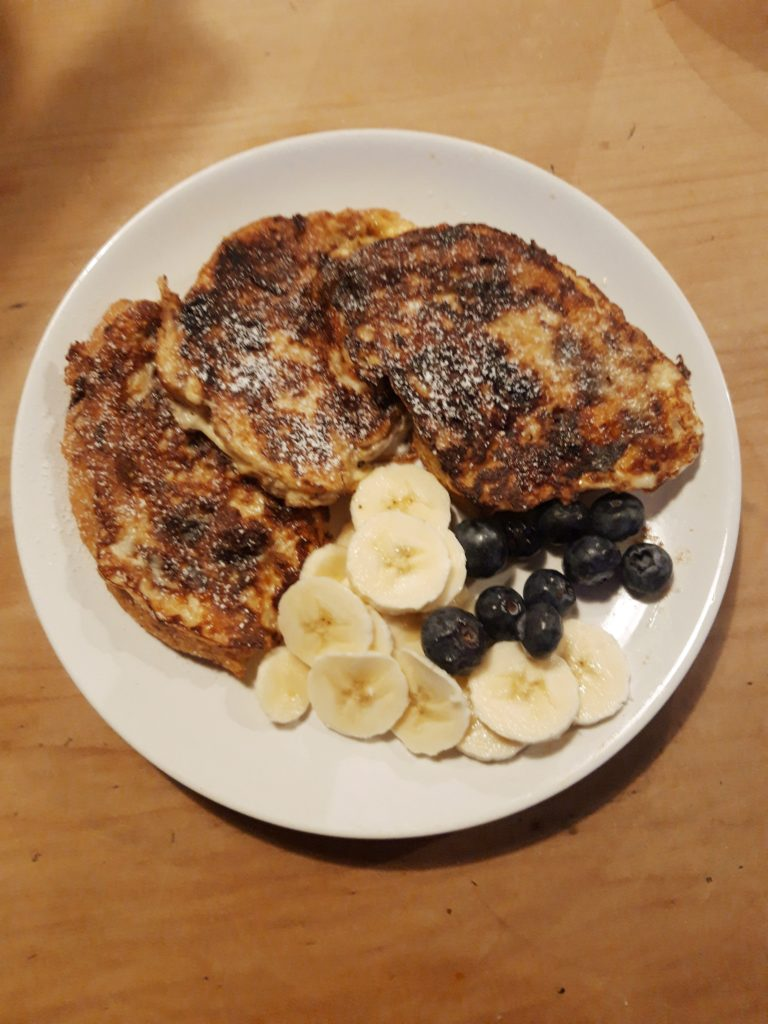A white plate of French Toast with bananas and blueberries.