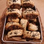 An oven dish piled high with small vegetable sausage rolls