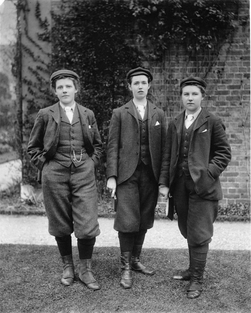 Photograph belonging to Kew's Guild collection showing three female Kew gardeners dressed in tweed short rousers and caps- the outfit a boy might wear