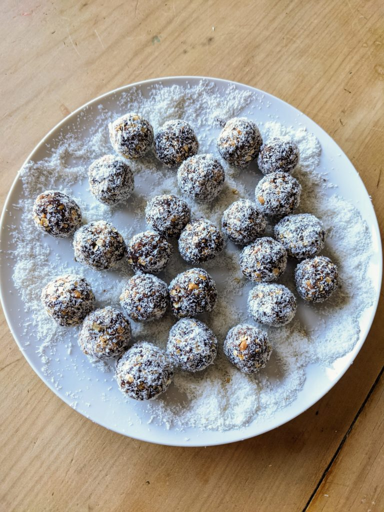 A white platter with a number of round, chocolate coconut covered energy balls