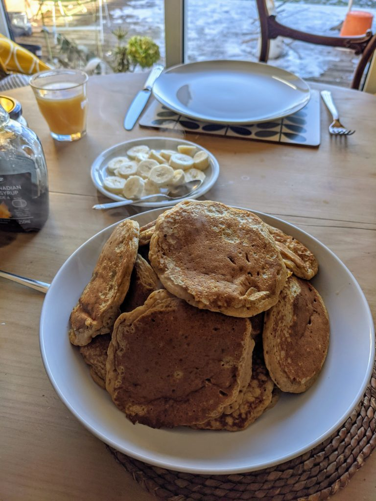 Sweet potato pancakes set on a white dish on a breakfast table