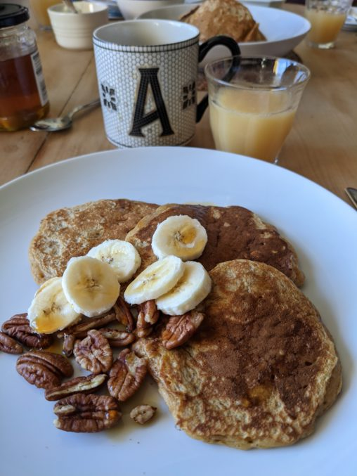 A breakfast table set with awhite platter with pancakes, chopped banana and pecan nuts