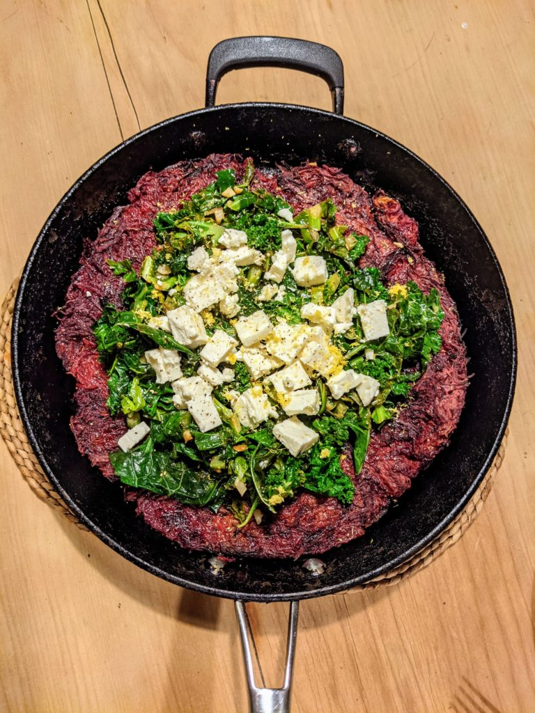 A pine table with a cast iron pan holding a Beetroot rösti with lemony greens and feta