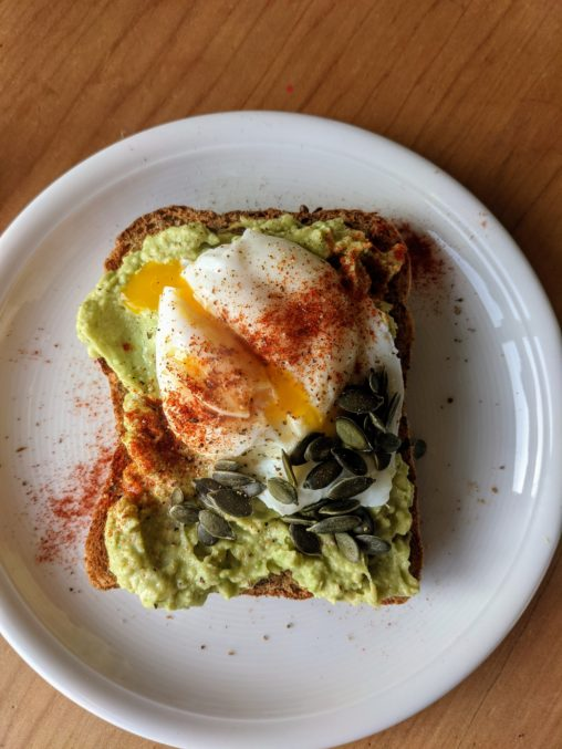 A white plate with a slice of toast topped with bright green avacadoa, a split poached egg garnished with smoked paprika
