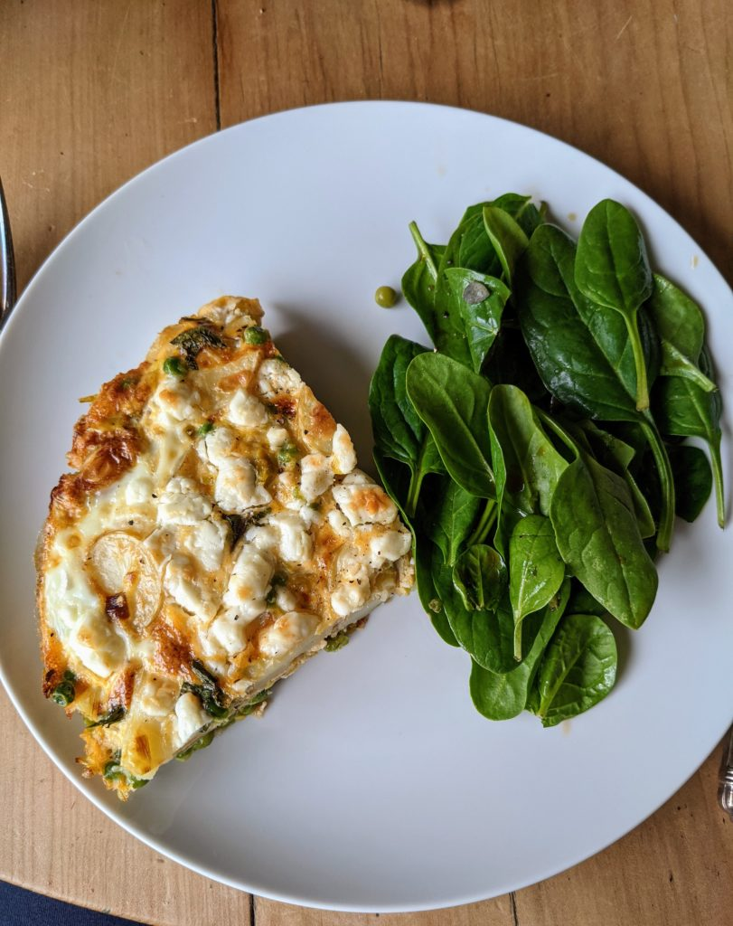 A white dish serving Leek, pea and feta frittata with a green salad
