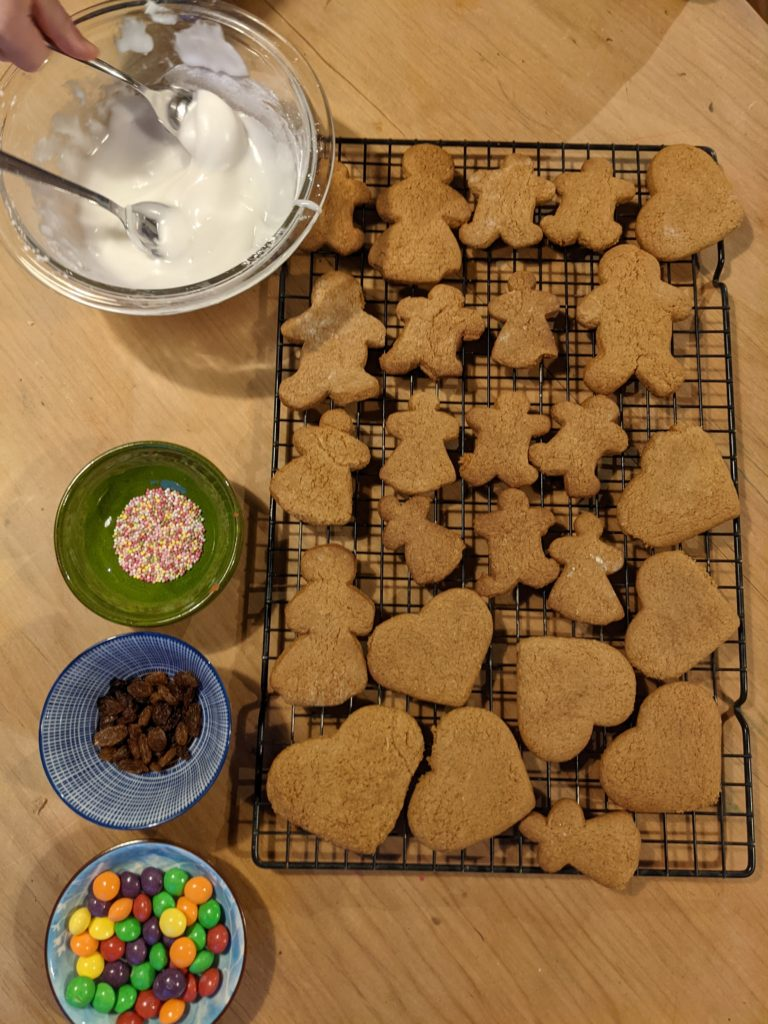 A table set for decorating some ginger bread biscuits with a cooling tray of biscuits, bowl of white icing and small bowls of sweets