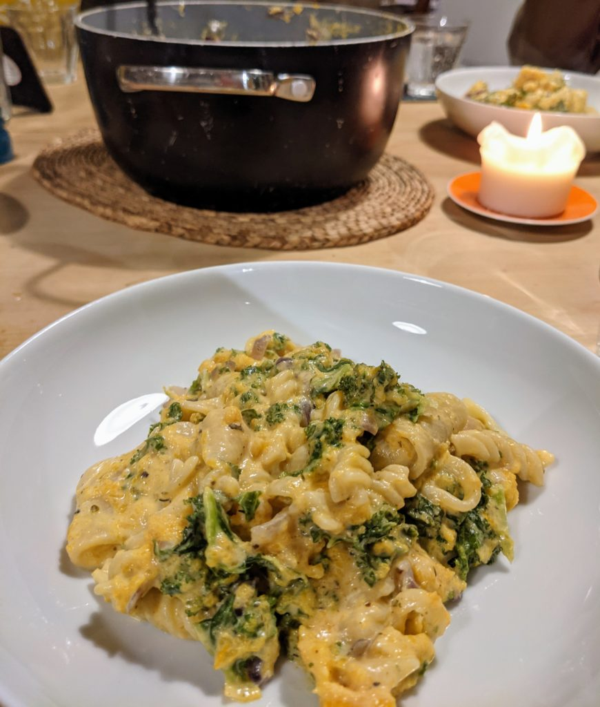 A table set for dinner with a black cooking pot, a candle and a white dish serving Creamy butternut squash and kale pasta
