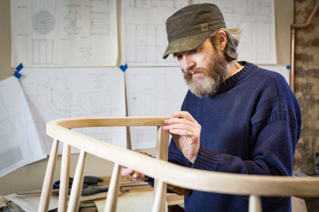 Maker Angus Ross is stood in his studio looking carefully at the light wooden frame of Resilience Bench, 2016.