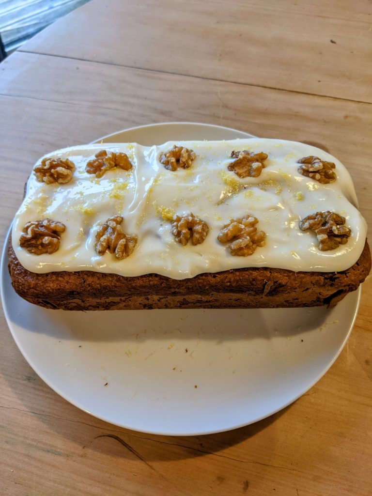 An iced parsnip and walnut cake topped with creamy icing and walnuts.