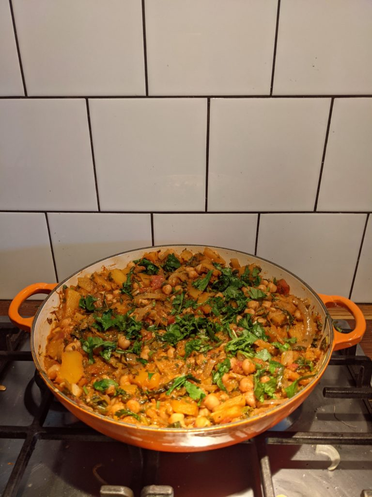 A large red, low cooking pan on the cooker with chickpea stew ready to be served