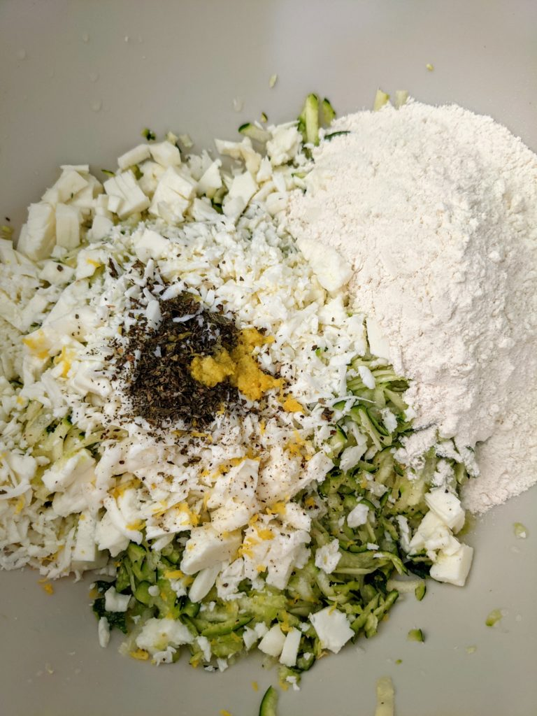A mound of dry ingredients of vegetables and flour on a table surface ready to be mixed